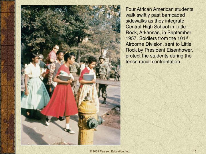 Four African American students walk swiftly past barricaded sidewalks as they integrate Central High School in Little Rock, Arkansas, in September 1957. Soldiers from the 101