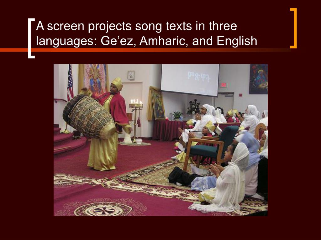 A screen projects song texts in three languages: Ge'ez, Amharic, and English