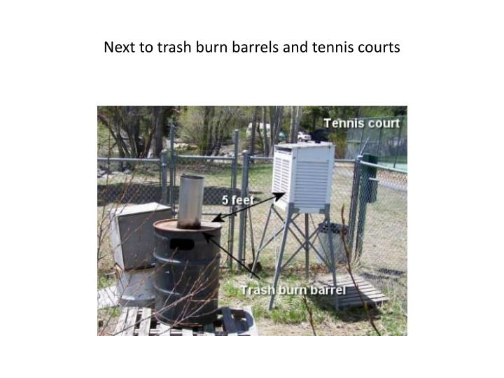 Next to trash burn barrels and tennis courts
