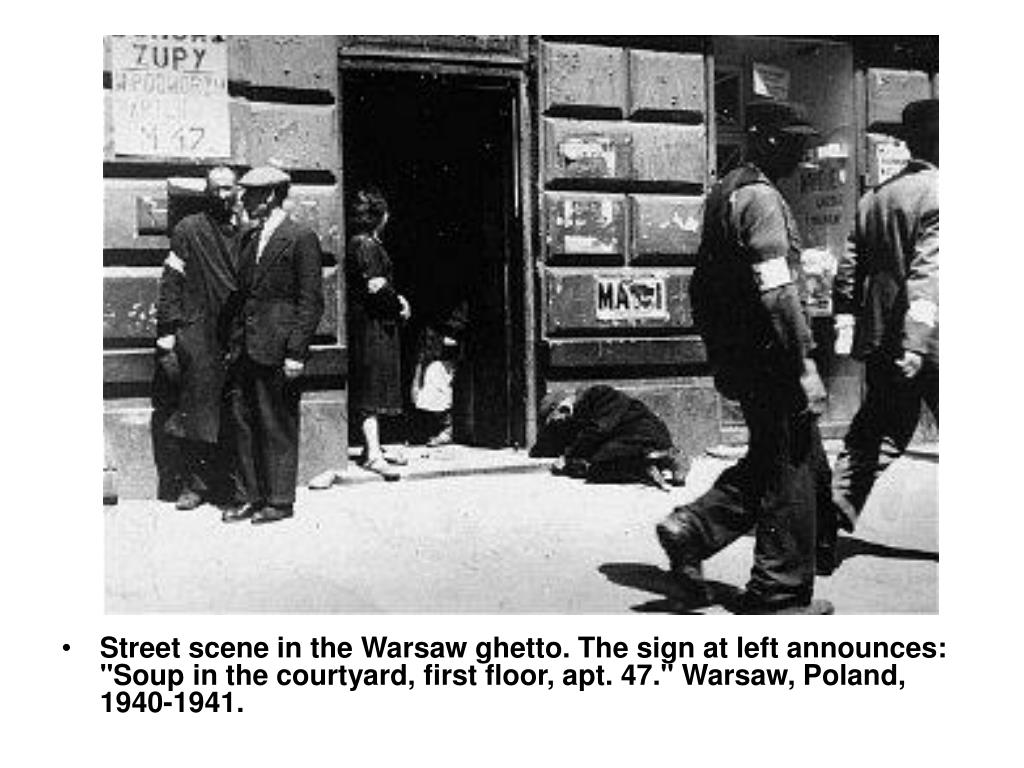 "Street scene in the Warsaw ghetto. The sign at left announces: ""Soup in the courtyard, first floor, apt. 47."" Warsaw, Poland, 1940-1941."