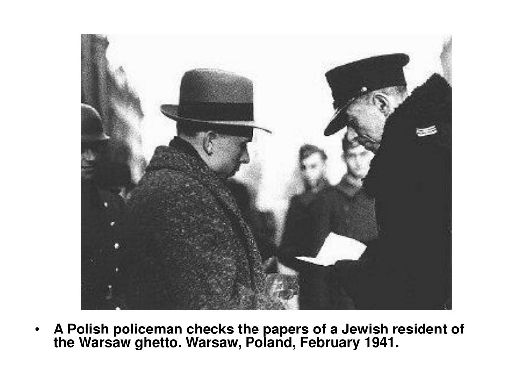 A Polish policeman checks the papers of a Jewish resident of the Warsaw ghetto. Warsaw, Poland, February 1941.