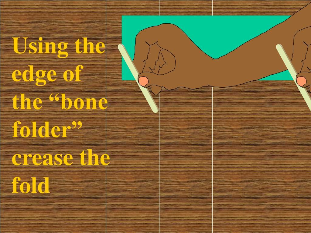 """Using the edge of the """"bone folder"""" crease the fold"""