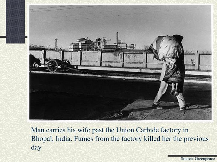Man carries his wife past the Union Carbide factory in Bhopal, India. Fumes from the factory killed her the previous day