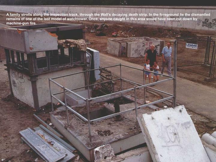 A family strolls along the inspection track, through the Wall's decaying death strip. In the foreground lie the dismantled remains of one of the last model of watchtower. Once, anyone caught in this area would have been cut down by machine-gun fire.