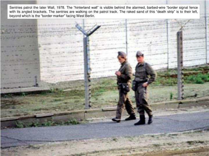 """Sentries patrol the later Wall, 1978. The """"hinterland wall"""" is visible behind the alarmed, barbed-wire """"border signal fence with its angled brackets. The sentries are walking on the patrol track. The raked sand of this """"death strip"""" is to their left, beyond which is the """"border marker"""" facing West Berlin."""