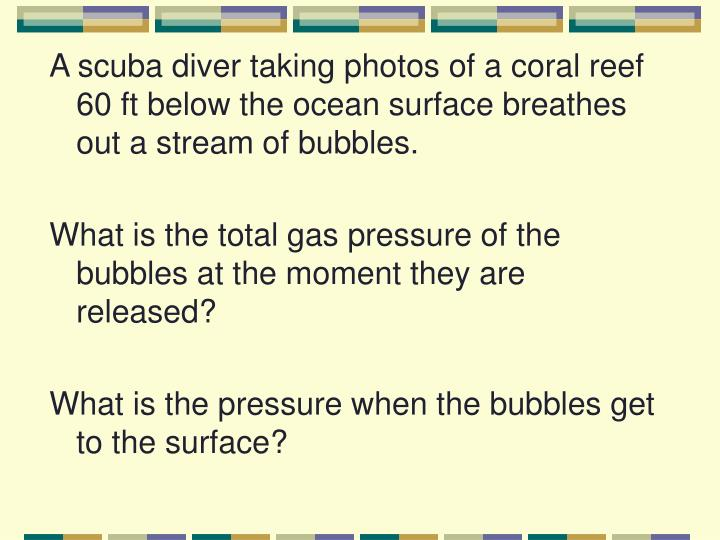 A scuba diver taking photos of a coral reef 60 ft below the ocean surface breathes out a stream of bubbles.