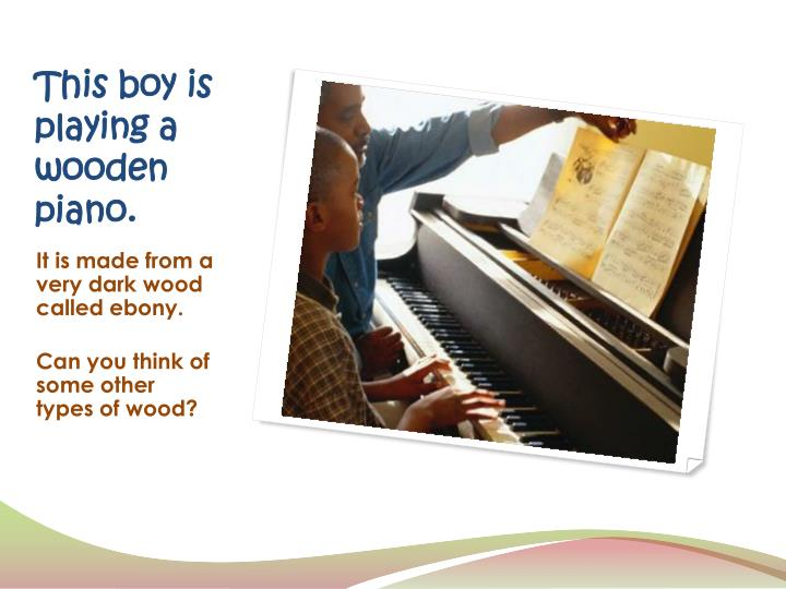 This boy is playing a wooden piano.