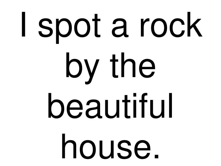 I spot a rock by the beautiful house.