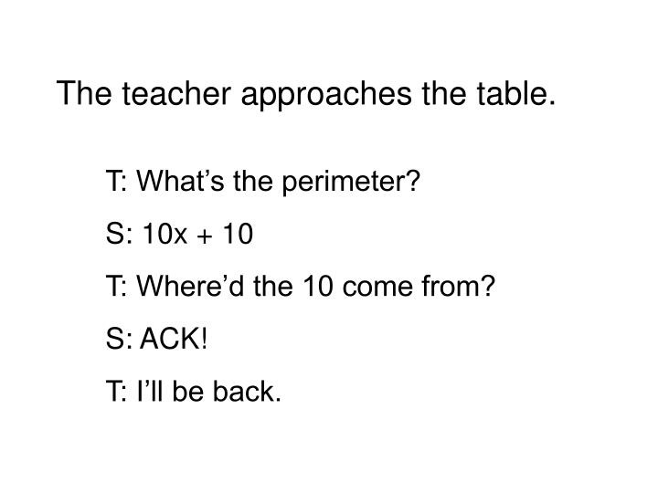 The teacher approaches the table.