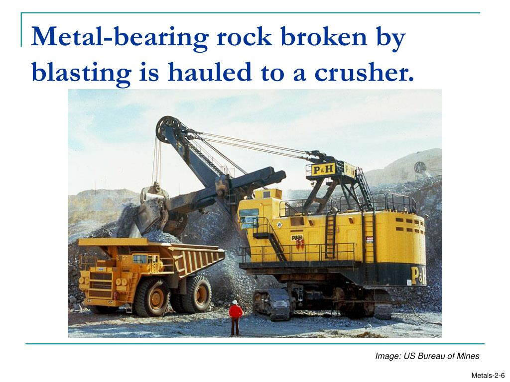 Metal-bearing rock broken by blasting is hauled to a crusher.