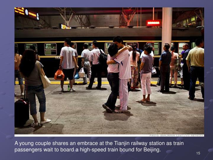 A young couple shares an embrace at the Tianjin railway station as train passengers wait to board a high-speed train bound for Beijing.