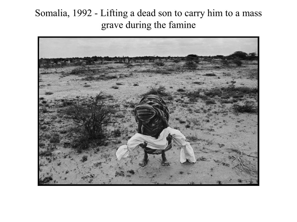 Somalia, 1992 - Lifting a dead son to carry him to a mass grave during the famine