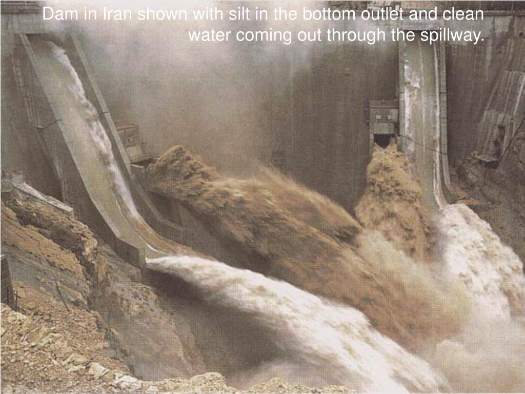 Dam in Iran shown with silt in the bottom outlet and clean water coming out through the spillway.