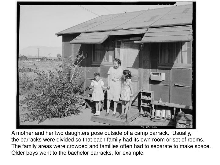 A mother and her two daughters pose outside of a camp barrack.  Usually,