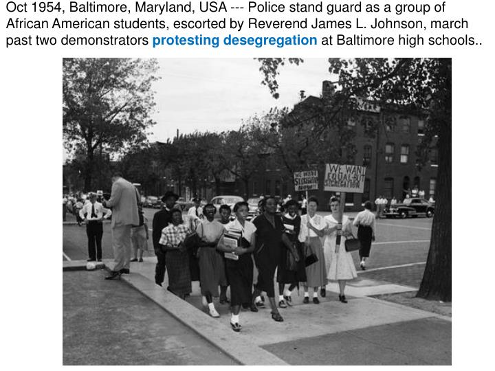 Oct 1954, Baltimore, Maryland, USA --- Police stand guard as a group of African American students, escorted by Reverend James L. Johnson, march past two demonstrators