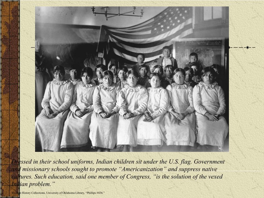 Dressed in their school uniforms, Indian children sit under the U.S. flag. Government