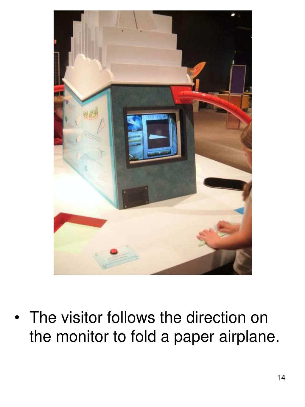 The visitor follows the direction on the monitor to fold a paper airplane.
