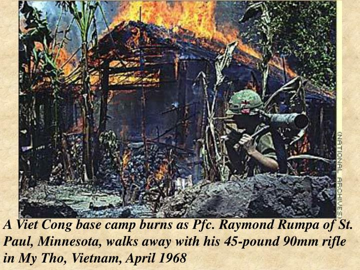 A Viet Cong base camp burns as Pfc. Raymond Rumpa of St. Paul, Minnesota, walks away with his 45-pound 90mm rifle in My Tho, Vietnam, April 1968