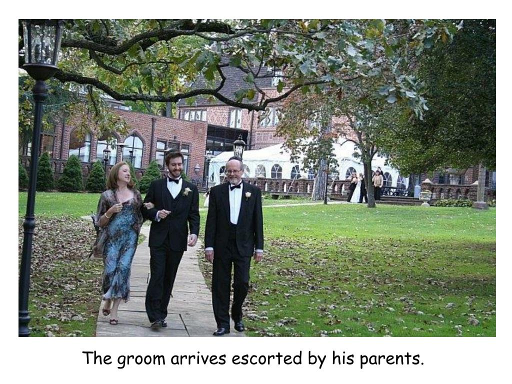 The groom arrives escorted by his parents.