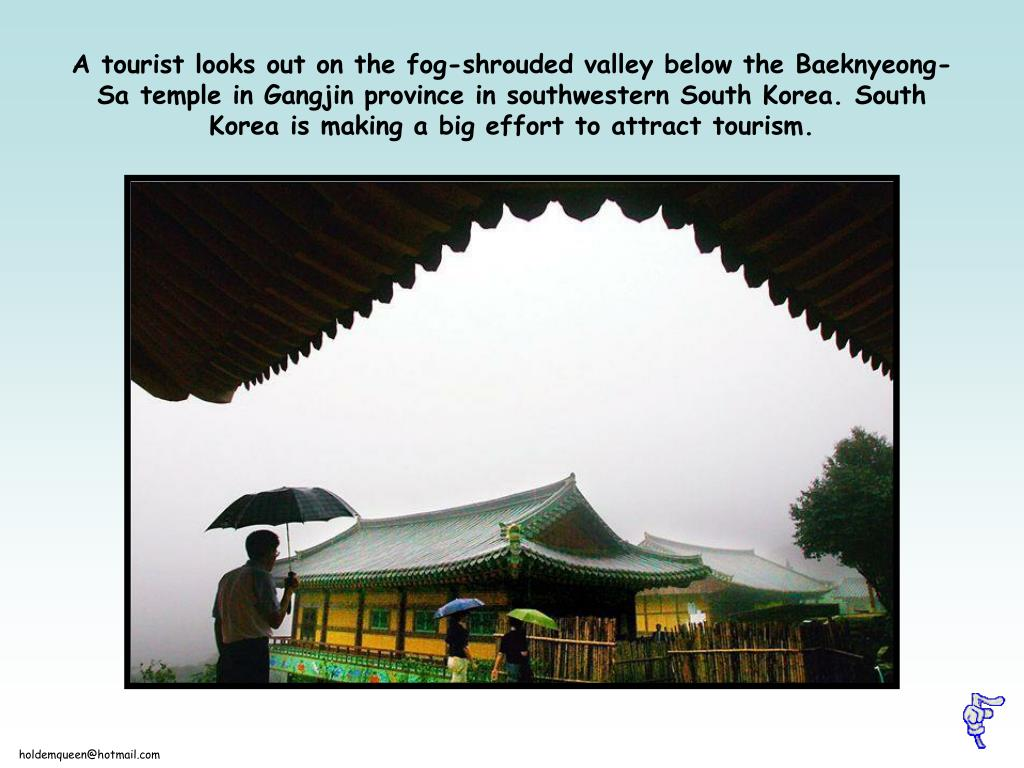 A tourist looks out on the fog-shrouded valley below the Baeknyeong-Sa temple in Gangjin province in southwestern South Korea. South Korea is making a big effort to attract tourism.