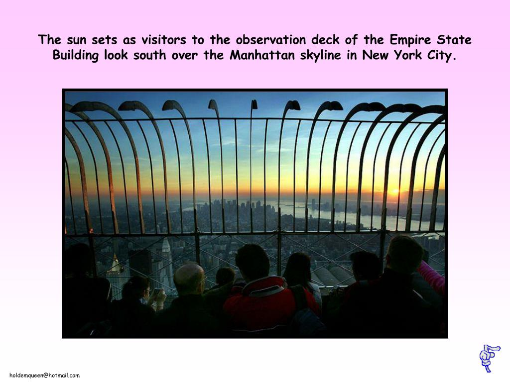 The sun sets as visitors to the observation deck of the Empire State Building look south over the Manhattan skyline in New York City.