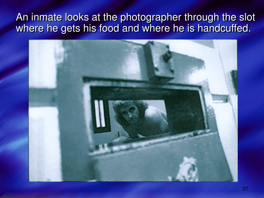 An inmate looks at the photographer through the slot
