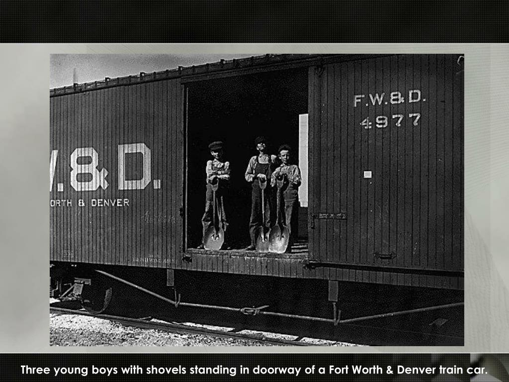 Three young boys with shovels standing in doorway of a Fort Worth & Denver train car.