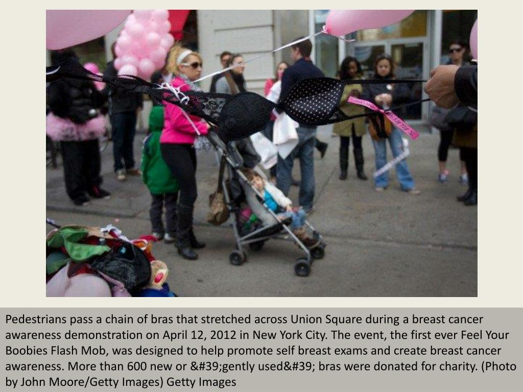 Pedestrians pass a chain of bras that stretched across Union Square during a breast cancer awareness demonstration on April 12, 2012 in New York City. The event, the first ever Feel Your Boobies Flash Mob, was designed to help promote self breast exams and create breast cancer awareness. More than 600 new or 'gently used' bras were donated for charity. (Photo by John Moore/Getty Images) Getty Images