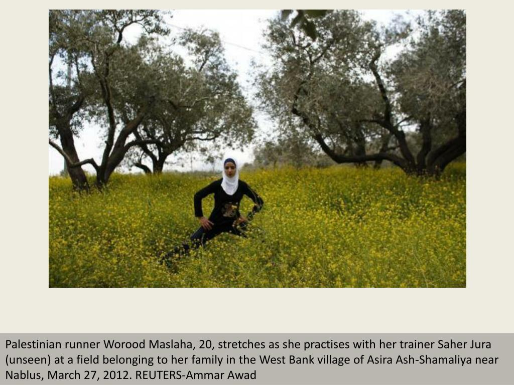 Palestinian runner Worood Maslaha, 20, stretches as she practises with her trainer Saher Jura (unseen) at a field belonging to her family in the West Bank village of Asira Ash-Shamaliya near Nablus, March 27, 2012. REUTERS-Ammar Awad