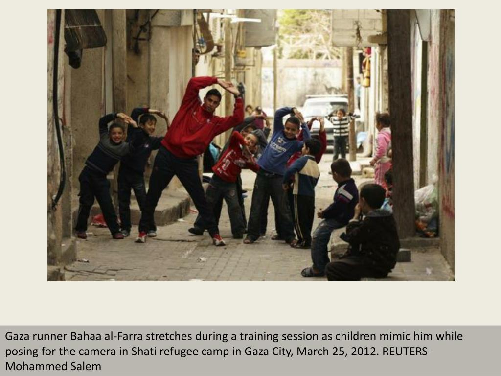 Gaza runner Bahaa al-Farra stretches during a training session as children mimic him while posing for the camera in Shati refugee camp in Gaza City, March 25, 2012. REUTERS- Mohammed Salem