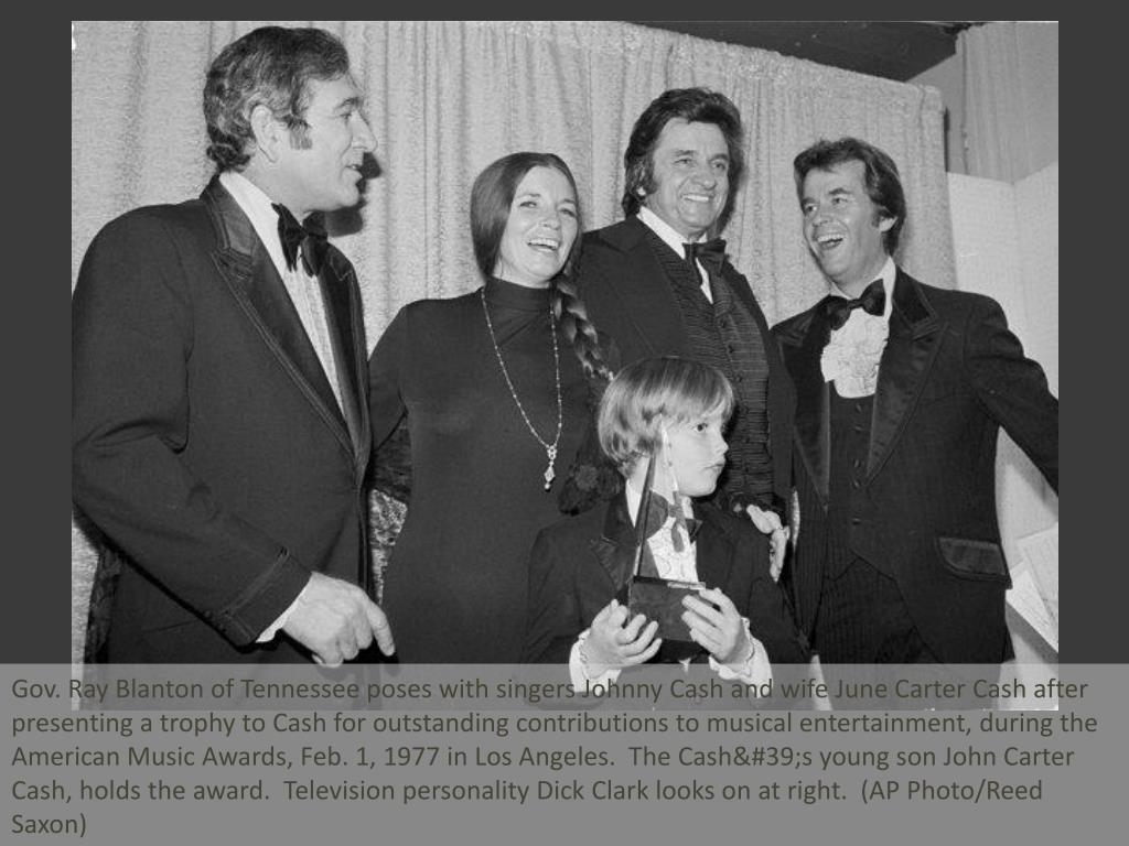 Gov. Ray Blanton of Tennessee poses with singers Johnny Cash and wife June Carter Cash after presenting a trophy to Cash for outstanding contributions to musical entertainment, during the American Music Awards, Feb. 1, 1977 in Los Angeles.  The Cash's young son John Carter Cash, holds the award.  Television personality Dick Clark looks on at right.  (AP Photo/Reed Saxon)