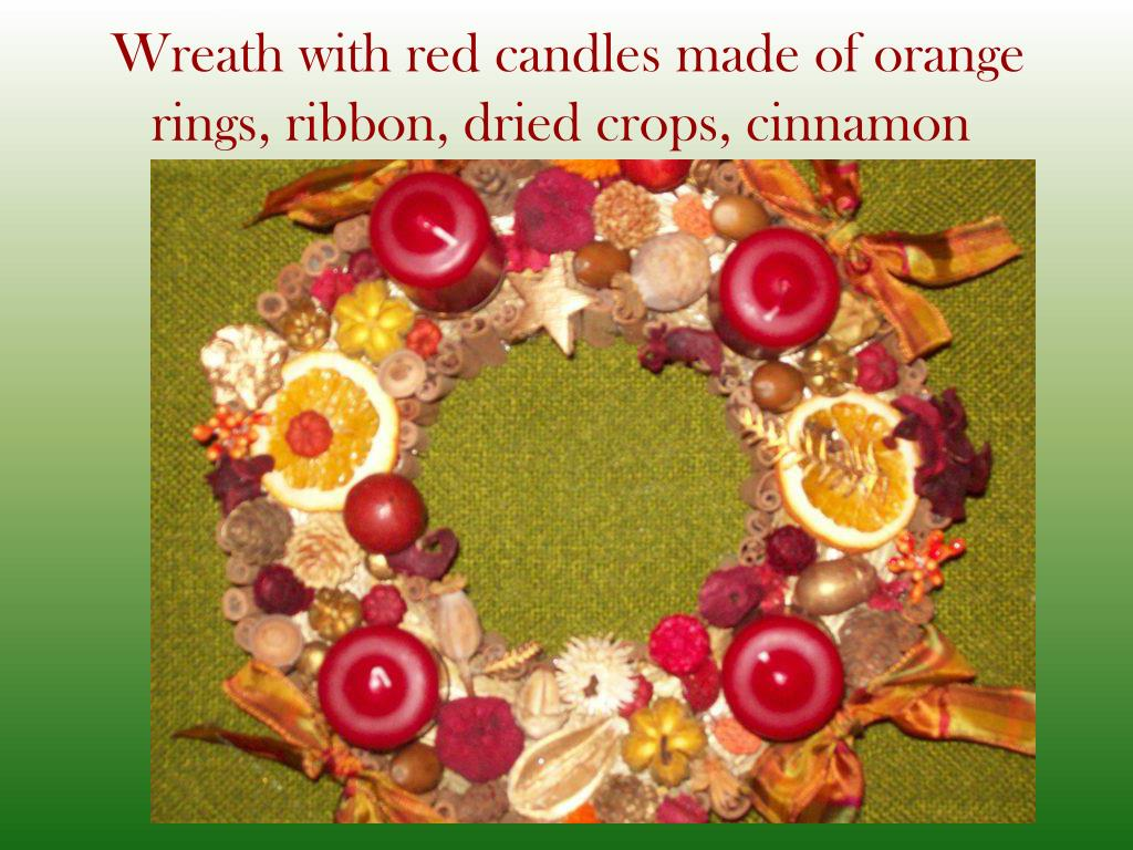 Wreath with red candles made of orange rings, ribbon, dried crops, cinnamon