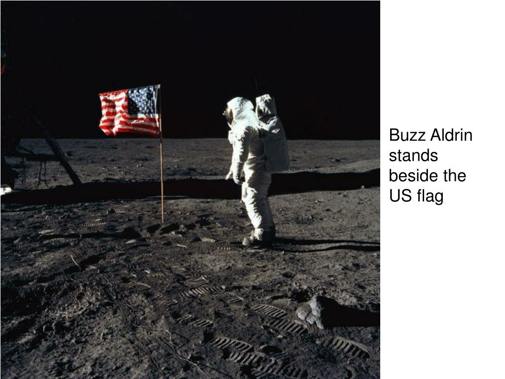 Buzz Aldrin stands beside the US flag