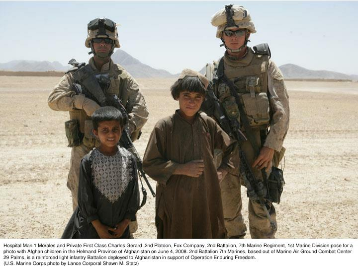 Hospital Man 1 Morales and Private First Class Charles Gerard ,2nd Platoon, Fox Company, 2nd Battalion, 7th Marine Regiment, 1st Marine Division pose for a photo with Afghan children in the Helmand Province of Afghanistan on June 4, 2008. 2nd Battalion 7th Marines, based out of Marine Air Ground Combat Center 29 Palms, is a reinforced light infantry Battalion deployed to Afghanistan in support of Operation Enduring Freedom.