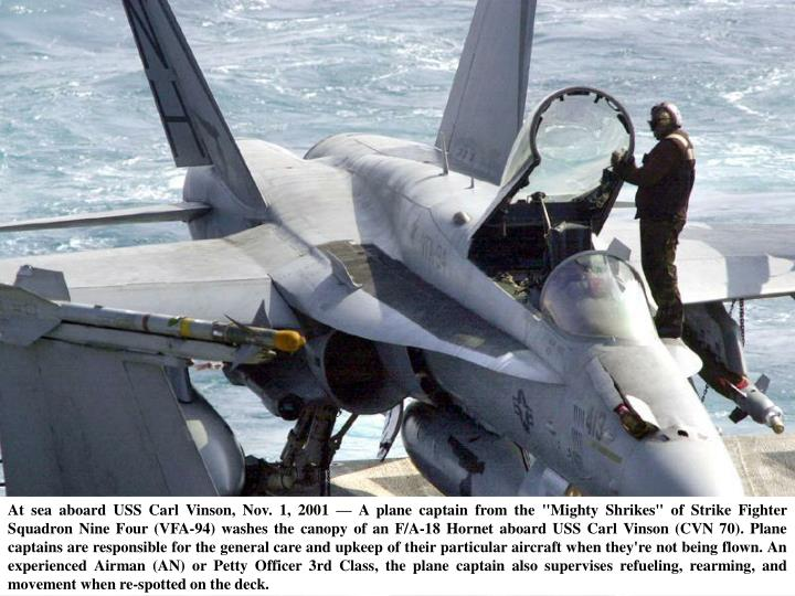 """At sea aboard USS Carl Vinson, Nov. 1, 2001 — A plane captain from the """"Mighty Shrikes"""" of Strike Fighter Squadron Nine Four (VFA-94) washes the canopy of an F/A-18 Hornet aboard USS Carl Vinson (CVN 70). Plane captains are responsible for the general care and upkeep of their particular aircraft when they're not being flown. An experienced Airman (AN) or Petty Officer 3rd Class, the plane captain also supervises refueling, rearming, and movement when re-spotted on the deck."""