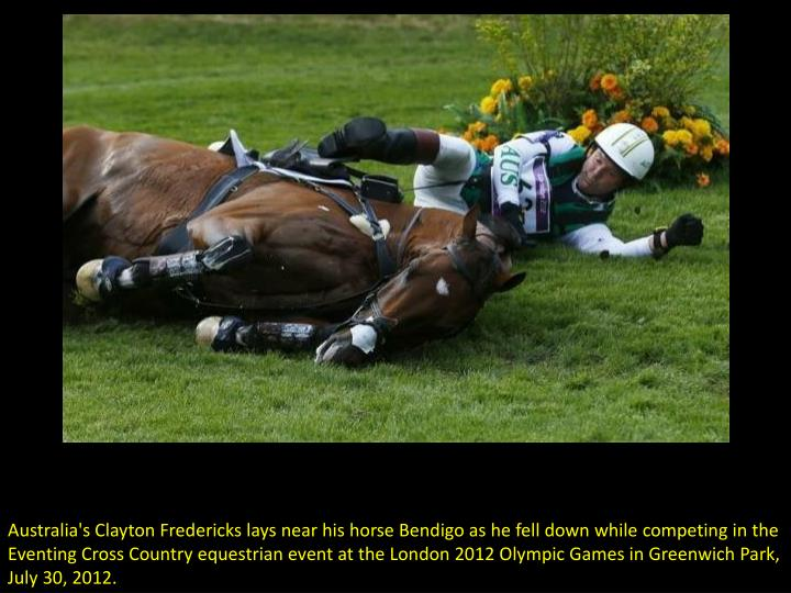 Australia's Clayton Fredericks lays near his horse Bendigo as he fell down while competing in the Ev...
