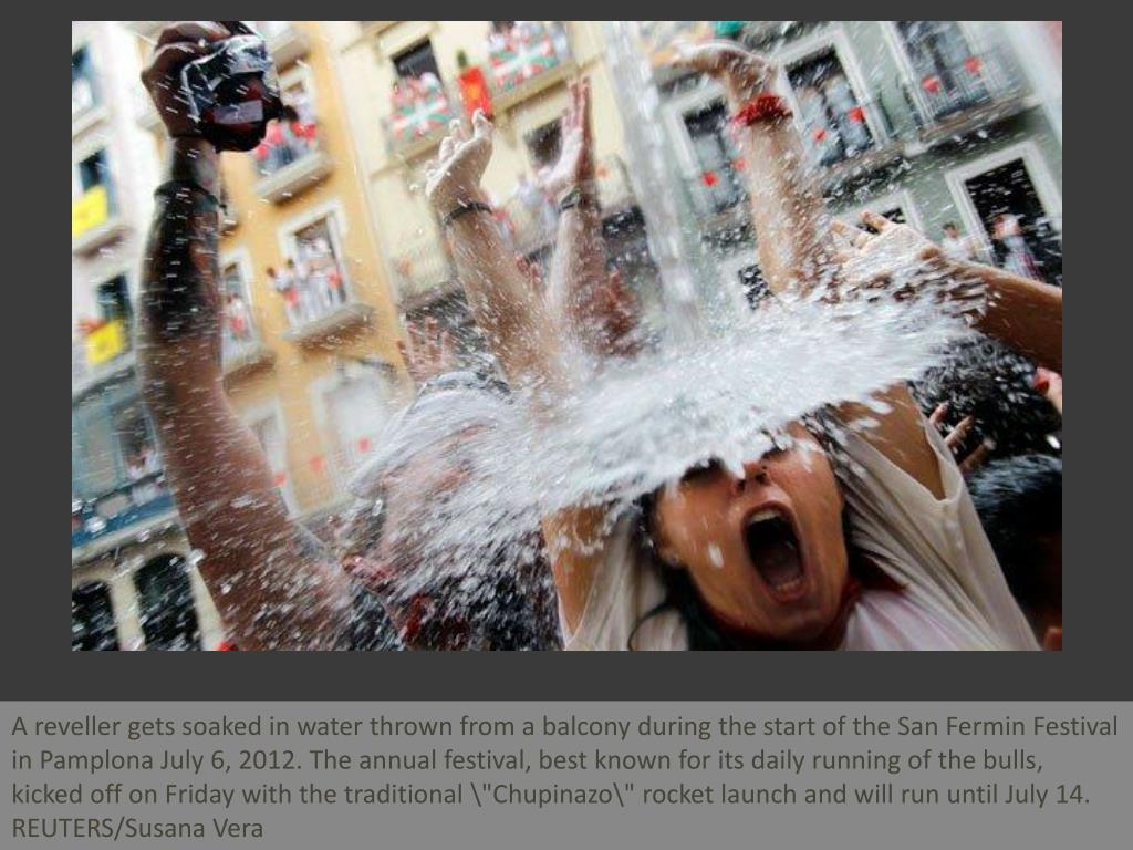 "A reveller gets soaked in water thrown from a balcony during the start of the San Fermin Festival in Pamplona July 6, 2012. The annual festival, best known for its daily running of the bulls, kicked off on Friday with the traditional ""Chupinazo\"" rocket launch and will run until July 14. REUTERS/Susana Vera"