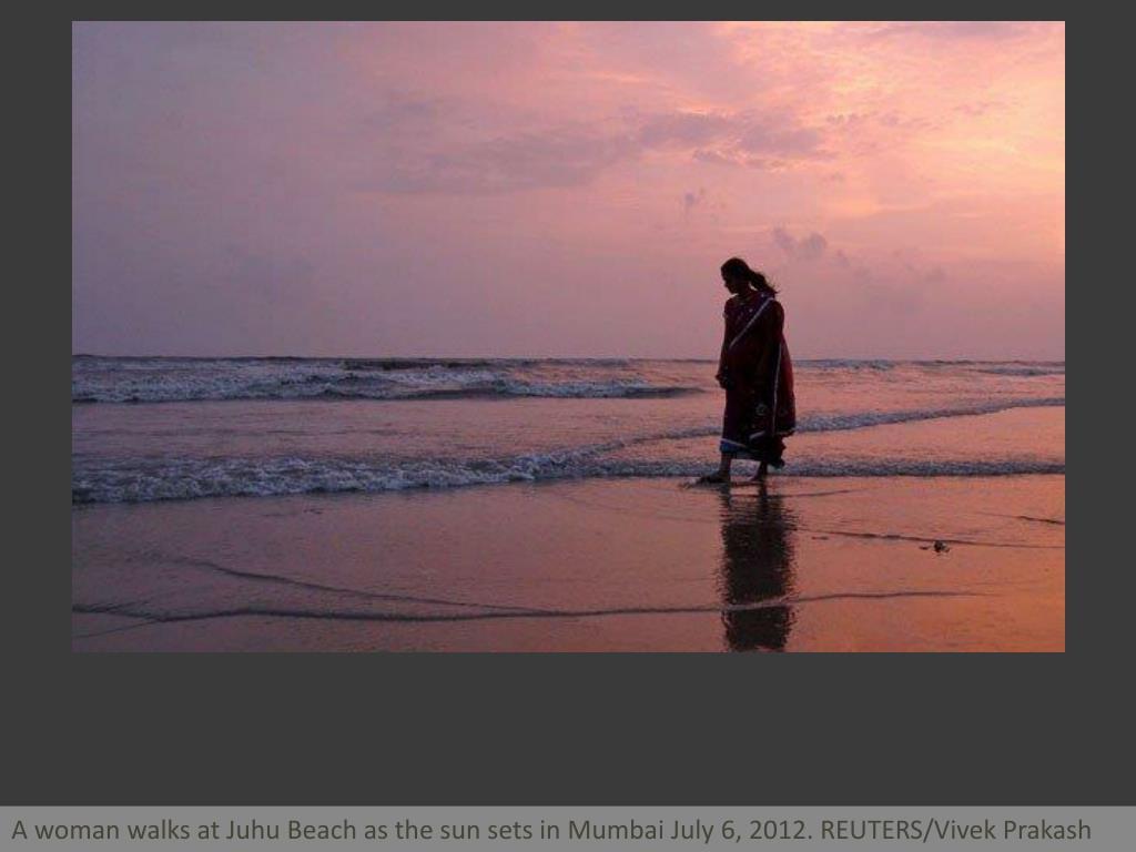A woman walks at Juhu Beach as the sun sets in Mumbai July 6, 2012. REUTERS/Vivek Prakash