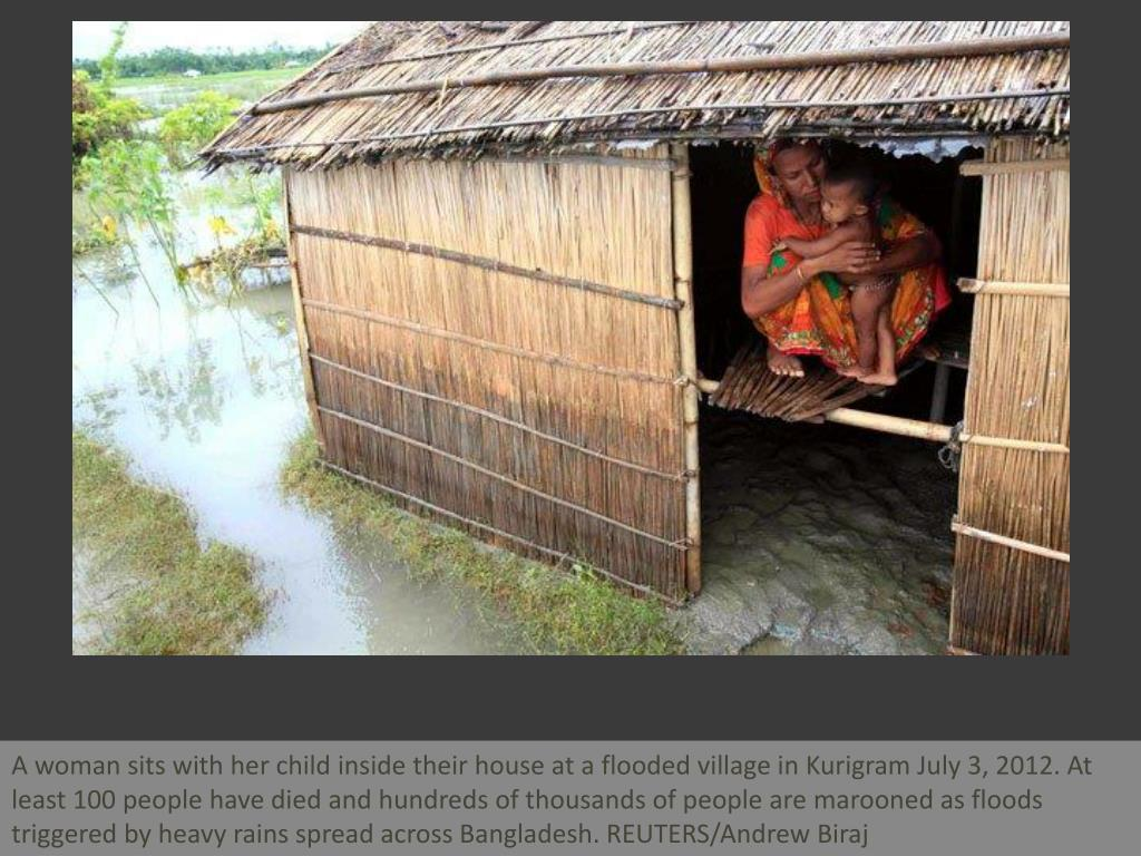 A woman sits with her child inside their house at a flooded village in Kurigram July 3, 2012. At least 100 people have died and hundreds of thousands of people are marooned as floods triggered by heavy rains spread across Bangladesh. REUTERS/Andrew Biraj
