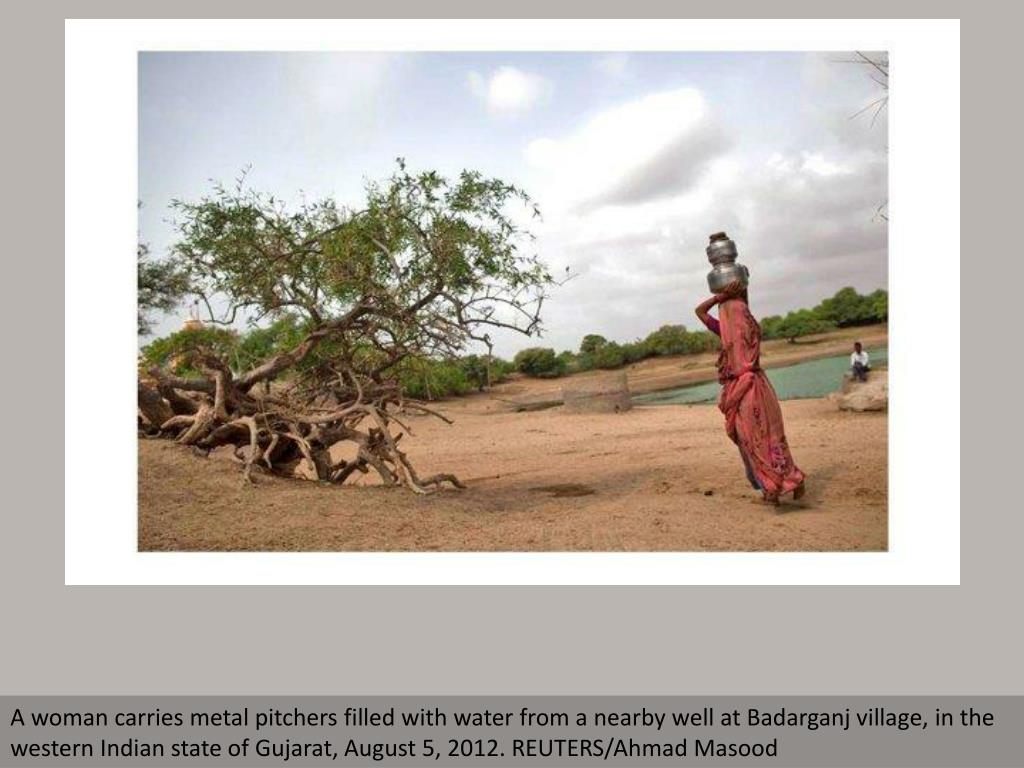 A woman carries metal pitchers filled with water from a nearby well at Badarganj village, in the western Indian state of Gujarat, August 5, 2012. REUTERS/Ahmad Masood