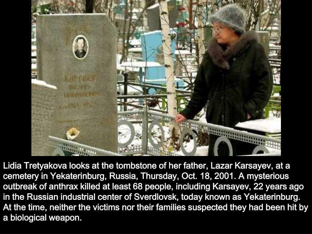 Lidia Tretyakova looks at the tombstone of her father, Lazar Karsayev, at a cemetery in Yekaterinburg, Russia, Thursday, Oct. 18, 2001. A mysterious outbreak of anthrax killed at least 68 people, including Karsayev, 22 years ago in the Russian industrial center of Sverdlovsk, today known as Yekaterinburg. At the time, neither the victims nor their families suspected they had been hit by a biological weapon.