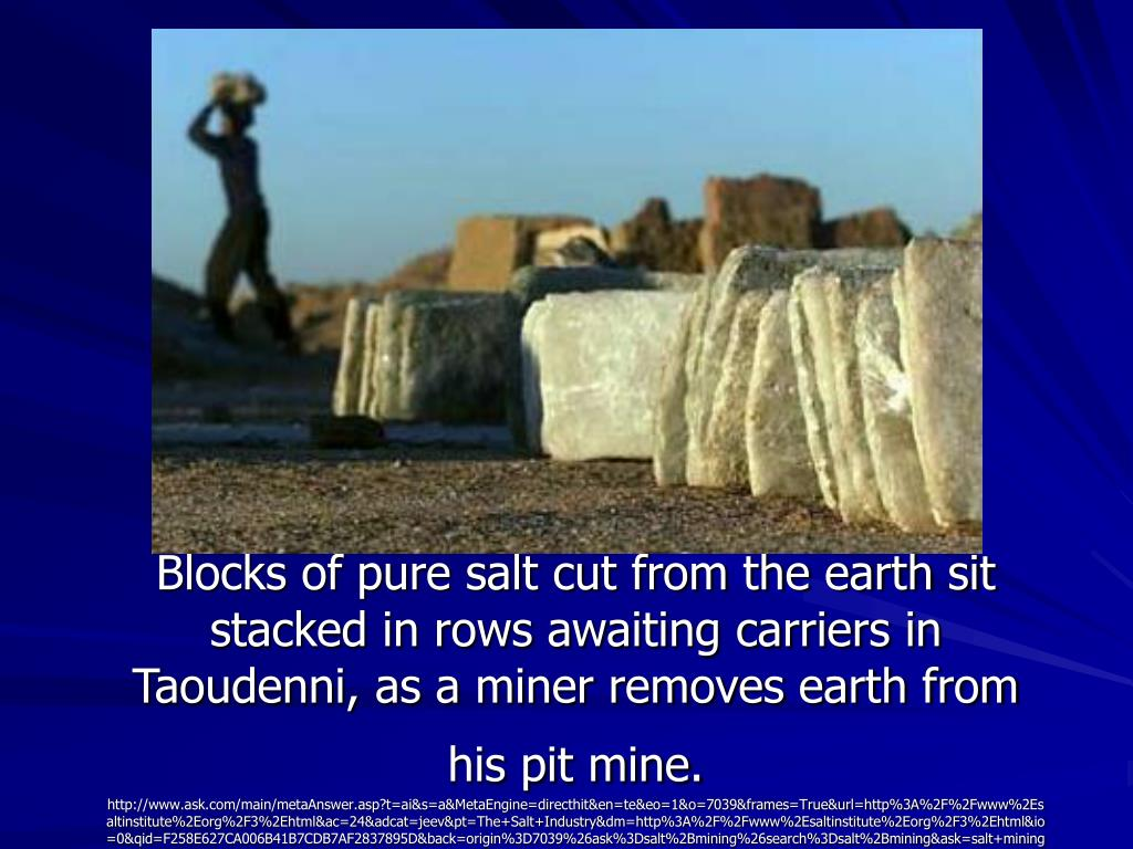 Blocks of pure salt cut from the earth sit stacked in rows awaiting carriers in Taoudenni, as a miner removes earth from his pit mine.