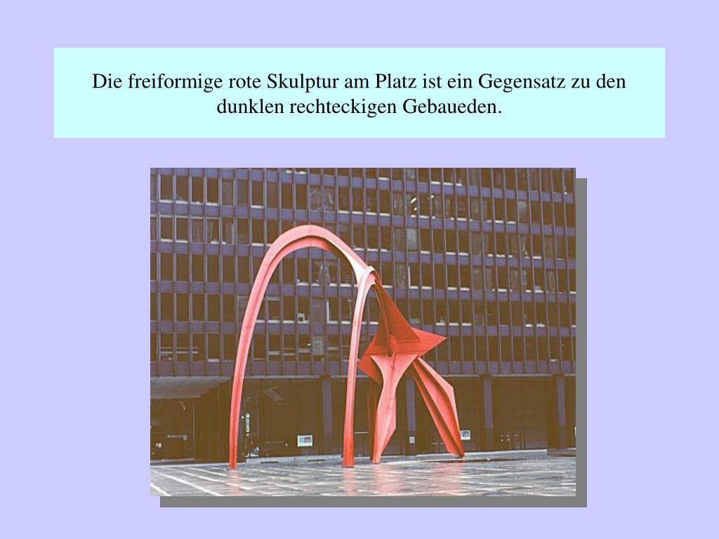Die freiformige rote Skulptur am Platz ist ein Gegensatz zu den dunklen rechteckigen Gebaueden.