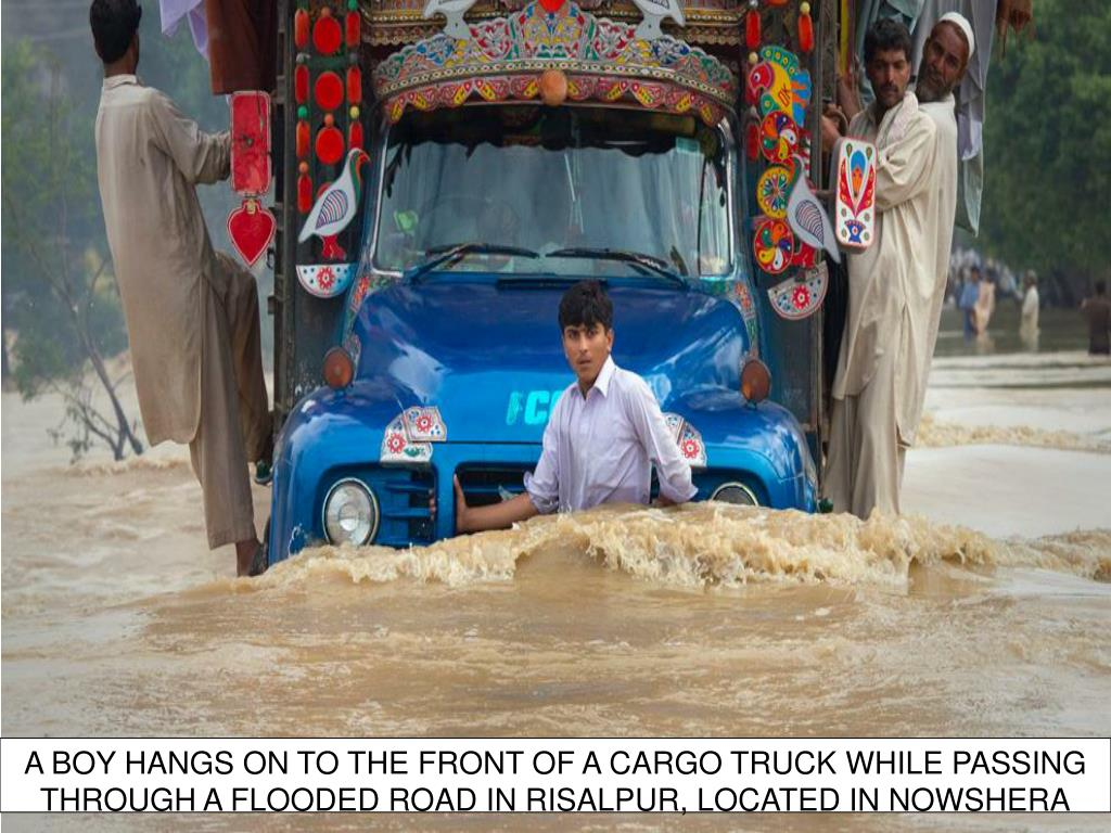A BOY HANGS ON TO THE FRONT OF A CARGO TRUCK WHILE PASSING THROUGH A FLOODED ROAD IN RISALPUR, LOCATED IN NOWSHERA