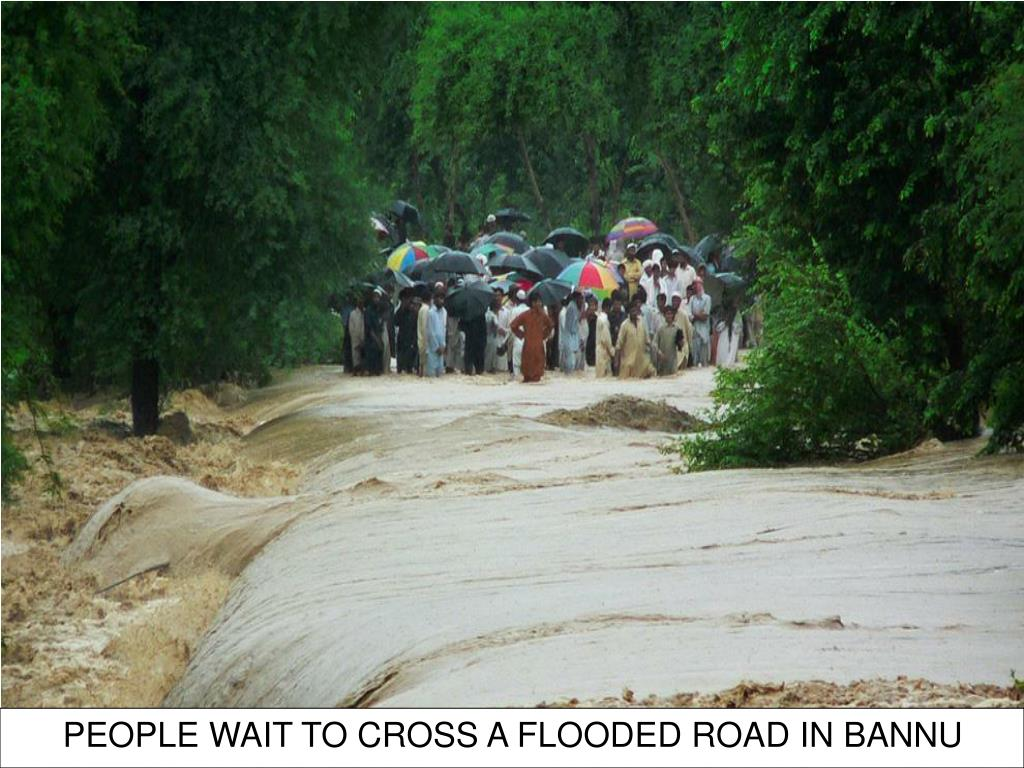 PEOPLE WAIT TO CROSS A FLOODED ROAD IN BANNU