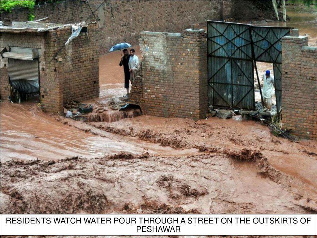 RESIDENTS WATCH WATER POUR THROUGH A STREET ON THE OUTSKIRTS OF PESHAWAR