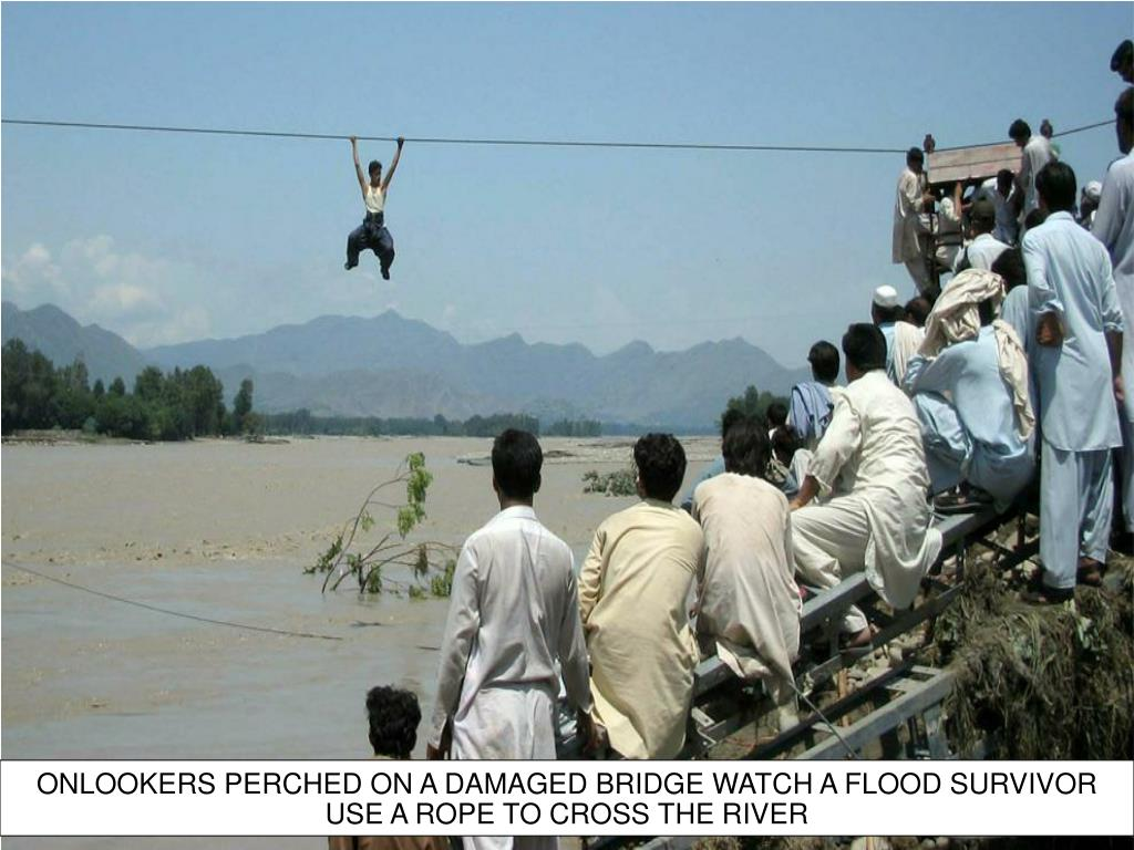 ONLOOKERS PERCHED ON A DAMAGED BRIDGE WATCH A FLOOD SURVIVOR USE A ROPE TO CROSS THE RIVER