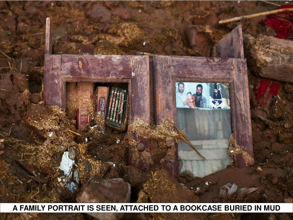 A FAMILY PORTRAIT IS SEEN, ATTACHED TO A BOOKCASE BURIED IN MUD