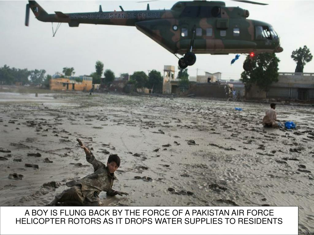A BOY IS FLUNG BACK BY THE FORCE OF A PAKISTAN AIR FORCE HELICOPTER ROTORS AS IT DROPS WATER SUPPLIES TO RESIDENTS
