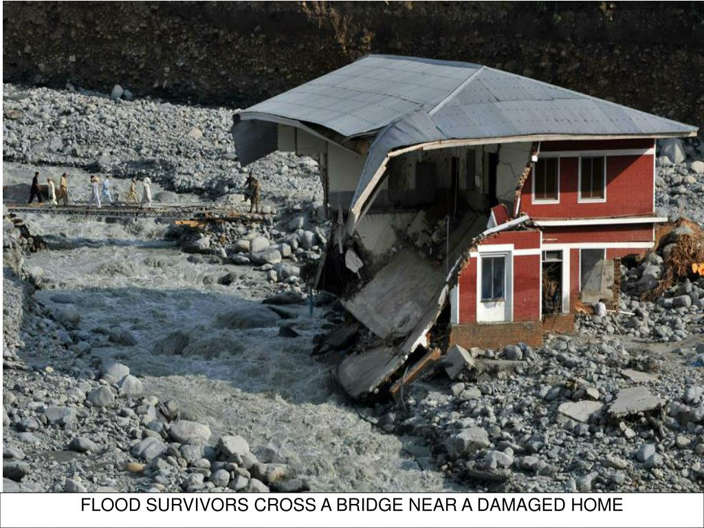 FLOOD SURVIVORS CROSS A BRIDGE NEAR A DAMAGED HOME